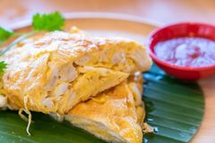 Thai style crab Omelette. Thai Omelette with crab, fried egg with crab meat, thai famous street food and restaurant cuisine on wooden table royalty free stock images