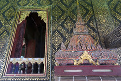 Thai-style decorated window and gilded wall, with scripture box on carved wooden shelf at Wat Mahathat Temple Royalty Free Stock Photo