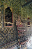 Thai-style decorated window and gilded wall, with scripture box on carved wooden shelf at Wat Mahathat Temple Stock Photos