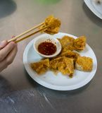 Thai style deep-fried pork dumpling serving with spicy plum sauce on white plate isolated on silver stainless steel table stock image