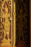 Thai style golden deva  carving with handcraft  on wood. Thai Traditional art with wood engraving  in Thai style on the door of the temple in the north of Royalty Free Stock Photos