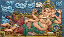 Thai style handcraft of ganesh hindu god on wall. Low relief cement Thai style handcraft of ganesh hindu god on wall, artwork for d?cor made from stucco work Royalty Free Stock Image