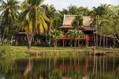 Thai style luxury wooden house. Thai style luxury traditional wooden house with coconut garden near the pond with refletion on water, Thailand Stock Images