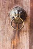 Thai style metal lion door knocker on wooden door Stock Images