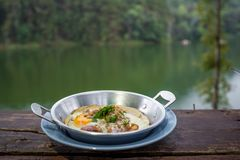Thai Style Omelet in plate on the wooden table with the river view. On behind Royalty Free Stock Photos
