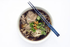 Thai Style Rice Noodles Soup with Beef. Thai Style Beef Rice Noodles Soup in Ceramic Bowl on White Fabric Background Royalty Free Stock Photography