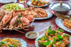 Thai style set of seafood insist of Thai steamed curry fish in banana leaf cups decorated with basil leaf, (Hor Mok Pla). Steamed crab/prawn/shrimp with seafood Royalty Free Stock Image