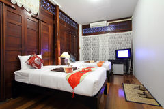Thai style tropical hotel bedroom. Oriental style resort bedroom with Asian theme Stock Image