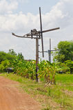 Thai style windmill with soil road in countryside Stock Photography