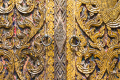 Thai style wooden door with brass knockers Stock Images