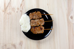 Thai-styled grilled pork and sticky rice. It's among most popular street foods in Thailand Royalty Free Stock Photos