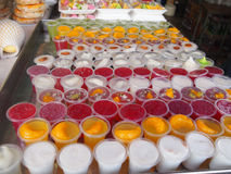 Thai sweets in a traditional Thai Bazaar. A beautiful fruit jellies of different Thai fruits, colored desserts, exotic food, refreshments to tourists Royalty Free Stock Photos