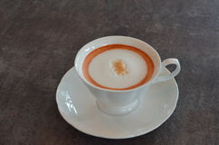 Thai Tea. Hot Thai milk tea late in white cup on wooden table royalty free stock photos