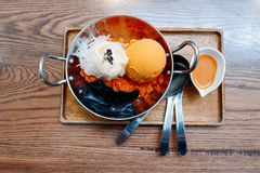 Thai tea ice cream served in stainless steel cups and wooden tray. Thai tea ice cream served in stainless steel cups and wooden tray royalty free stock images