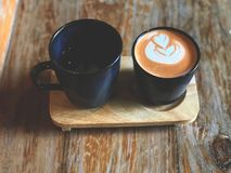 Thai tea latte art and hot drink in Black cup on wooden tray. With natural light. Favorite tea in Thailand stock photos