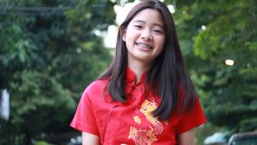 Thai teen beautiful girl in Chinese dress, happy new year and give gift, relax and smile. Portrait of thai teen beautiful girl in Chinese dress, happy new year