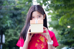 Thai teen beautiful girl in Chinese dress, happy new year and give gift, relax and smile. Stock Photos