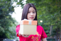 Thai teen beautiful girl in Chinese dress, happy new year and give gift, relax and smile. Royalty Free Stock Images