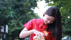 Thai teen beautiful girl in Chinese dress, happy new year and open box gift, smile and very happy. stock video
