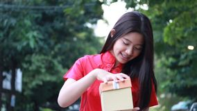 Thai teen beautiful girl in Chinese dress, happy new year and open box gift, smile and very happy. Portrait of thai teen beautiful girl in Chinese dress, happy