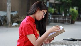 Thai teen beautiful girl in Chinese dress read a book. stock video footage