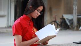 Thai teen beautiful girl in Chinese dress read a book. Portrait of thai teen beautiful girl in Chinese dress read a book stock video