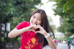 Thai teen beautiful girl in Chinese dress, relax and smile. Royalty Free Stock Photography
