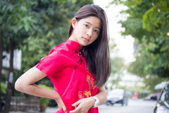 Thai teen beautiful girl in Chinese dress, relax and smile. Royalty Free Stock Photo