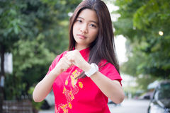 Thai teen beautiful girl in Chinese dress, relax and smile. Stock Photo