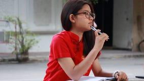 Thai teen beautiful girl in Chinese dress write a book.