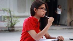 Thai teen beautiful girl in Chinese dress write a book. Portrait of thai teen beautiful girl in Chinese dress write a book stock video footage