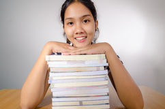 Thai teenage girl. Portrait of smiling teenage Thai girl with both hands on top of  a pile of paperback books, gray background Royalty Free Stock Photography