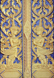 Thai temple door golden angle sculpture Royalty Free Stock Photography
