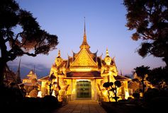 Thai temple glowing in golden light during sunset. Thai temple with a golden glow and guarded by two huge statues. Shot with a view of blue evening sky in Stock Image