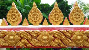Thai temple wall decoration. Cast the cement and painting gold color. About karma wheel for buddhism and thai art Royalty Free Stock Photo
