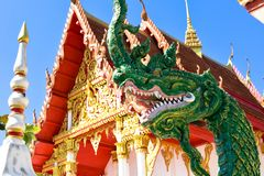 Thai temples in the Northeast. The green serpent statue is placed in front of the golden church on a clear day Stock Images