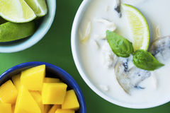 Thai Tom Kha Gai soup with mango and lime on green table Stock Image