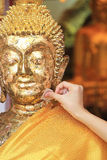 Thai tradition. Cover statue of Buddha with gold leaf Stock Photo