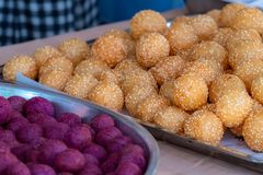 Thai traditional dessert. Deep fried sesame balls and deep fried sweet potato balls on stainless steel tray of seller. Purple royalty free stock image