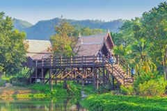 Thai traditional houses style along canal, Mueang Mallika hist. Oric site in Kanchanaburi, Thailand stock photography