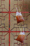 Thai traditional ice tea in bag hanging on red wall. Thai traditional ice tea in bag hanging on Chinese red wall stock photography