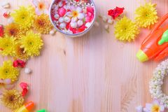 Thai traditional jasmine garland and Colorful flower in water bowls decorating and scented water, perfume, marly limestone. Pipe gun on wood background for Stock Photography
