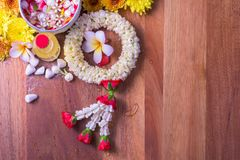 Thai traditional jasmine garland and Colorful flower in water bowls decorating and scented water, perfume, marly limestone. Pipe gun on wood background for Royalty Free Stock Photography