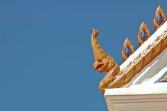 Thai traditional naga decoration on temple roof under blue sky Stock Images