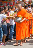 Thai traditional offering flowers to Buddhist monks. Flower alms offering festival at the beginning of Buddhist Lent in Saraburi, Thailand. Photo taken on July Stock Photography