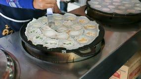 Local seller make make Thai sweetmeat, Kanom krok  at Sriyan mar. Thai traditional sweetmeat, Khanom krok is made of rice flour, coconut milk, sugar and Stock Images