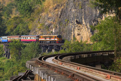 Thai trains running on death railways crossing kwai river in kan Stock Photos