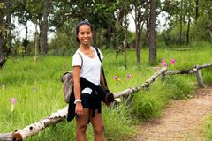 Thai trekking lady smiling during path of trail to Krachai flower field. In mountain Royalty Free Stock Photo