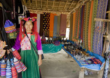 Thai Tribe Woman. Thai hill tribe woman in a colorful traditional costume selling handicraft in a bamboo stall Royalty Free Stock Images