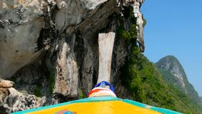 Thai troditional longtail boat swims under the karst mountain. Bright orange karst stslsctites hang over the juicy greens. Drops of sea water above the boat fly stock footage
